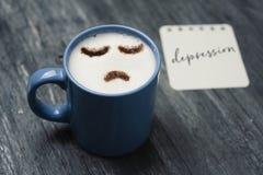 Filiżanka cappuccino z smutną twarzą zdjęcia royalty free