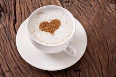 Filiżanka cappuccino z zmielonym cynamonem w postaci serca. zdjęcie stock