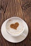 Filiżanka cappuccino z zmielonym cynamonem w postaci serca. zdjęcia stock
