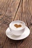 Filiżanka cappuccino z zmielonym cynamonem w postaci serca fotografia stock