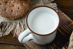 Filiżanka ciepły mleko i chleb na drewnianym tle Fotografia Stock