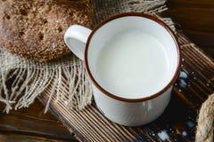 Filiżanka ciepły mleko i chleb na drewnianym tle Obraz Stock