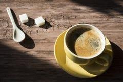 Filiżanka czarna kawa w żółtym kubku z łyżką i cukierem przeciw drewnianemu tłu, fotografia royalty free