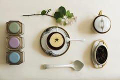 Filiżanka, dżem, jabłko i gałąź z kwiatami na białym stole, Obrazy Stock