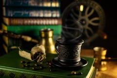 Filiżanka dekatyzować gorącą kawę, fasole, turek i kawowy ostrzarz na tle, Atmosfera biblioteka z starymi książkami wokoło na zmr zdjęcia stock