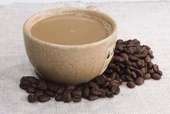 Filiżanka dojna kawa z kawowymi fasolami wokoło Obraz Royalty Free