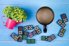 Filiżanka, domino i klingerytów kwiaty na błękitnym drewnianym backgr, Zdjęcia Royalty Free
