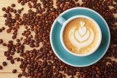 Filiżanka fragrant kawa w pianie na drewnianym stole Latte sztuka bean śniadanie kawa ideał wyizolował makro nadmiar białych zdjęcia royalty free
