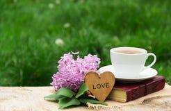 Filiżanka gorąca herbata, książka i bzy przeciw tłu zielona trawa, Romantyczny pojęcie Drewniana karta z sercem Obrazy Royalty Free