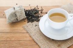 Filiżanka gorąca herbata na parciaku z wysuszonymi herbacianymi liśćmi przelewa się formularzową torbę Zdjęcie Royalty Free