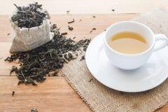 Filiżanka gorąca herbata na parciaku z wysuszonymi herbacianymi liśćmi przelewa się formularzową torbę na drewnianym stole z kopi Obraz Royalty Free