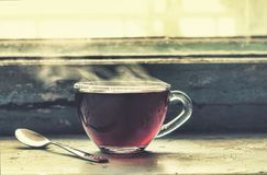 Filiżanka gorąca herbata przy okno Fotografia Stock