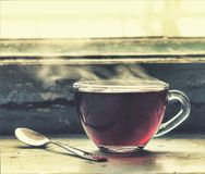 Filiżanka gorąca herbata przy okno Zdjęcie Stock