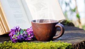 Filiżanka gorąca kawa blisko otwartej książki w lesie na fiszorku Odpoczynek w lesie na nature_ obrazy royalty free