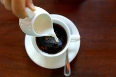 Filiżanka gorąca kawa i dolewanie z mlekiem, stawiająca dalej brown stół zdjęcia royalty free