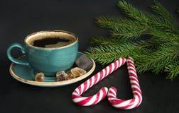 Filiżanka gorąca kawy i cukierku trzcina w kształcie serce na czarnym tle z choinką rozgałęzia się Zdjęcie Royalty Free