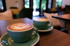 Filiżanka gorąca latte sztuki kawa na drewnianym stole Obrazy Royalty Free