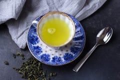 Filiżanka gorąca zielona herbata na ciemnym tle Gorący napój zielona herbata w porcelany filiżance, herbaciani liście Zdjęcia Royalty Free