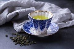 Filiżanka gorąca zielona herbata na ciemnym tle Gorący napój zielona herbata w porcelany filiżance, herbaciani liście Fotografia Stock