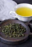 Filiżanka gorąca zielona herbata na ciemnym tle Gorący napój zielona herbata w porcelany filiżance, herbaciani liście Zdjęcia Stock