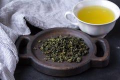 Filiżanka gorąca zielona herbata na ciemnym tle Gorący napój zielona herbata w porcelany filiżance, herbaciani liście Zdjęcie Royalty Free