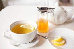 Filiżanka gorąca zielona herbata z cytryną na bielu stole Obrazy Royalty Free