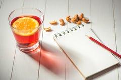 Filiżanka gorący boże narodzenie napój Rozmyślający wino z pomarańcze i notatnikiem Zdjęcia Royalty Free