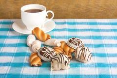 Filiżanka herbaciani i wyśmienicie ciastka na w kratkę tablecloth Obrazy Royalty Free