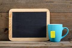 Filiżanka herbaciany i mały blackboard Obrazy Royalty Free