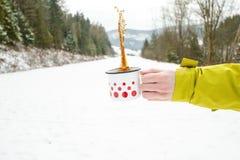 Filiżanka herbaciany mienie w kobiety ręce tło płatków śniegu biały niebieska zima Gorący napój z pianą snow i zimna pogoda przes Obraz Stock
