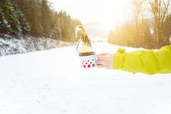 Filiżanka herbaciany mienie w kobiety ręce tło płatków śniegu biały niebieska zima Gorący napój z pianą snow i zimna pogoda przes zdjęcia stock