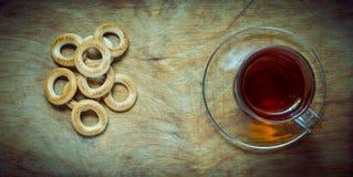 Filiżanka herbata, bagels suszy na starym wieśniaka stołu drewna tle Zdjęcie Royalty Free