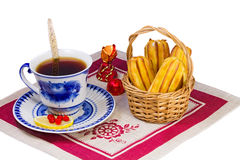 Filiżanka herbata, cukierki i torty w łozinowym koszu. Obrazy Royalty Free