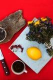 Filiżanka herbata, cytryna na czerwonym tle, jedzenie, napój, nóż i rozwidlenie, herbaciany czas, śniadaniowego czasu widok od ab Zdjęcie Stock