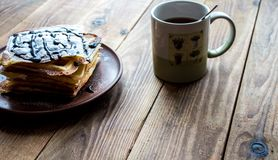 Filiżanka herbata i stos opłatki na drewnianym tle obrazy stock