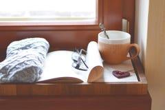 Filiżanka herbata, książka, szkła okno parapet zdjęcia stock