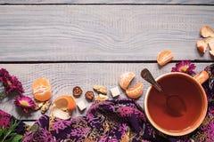 Filiżanka herbata, kwiaty i tangerine na białym drewnianym stole, obrazy stock