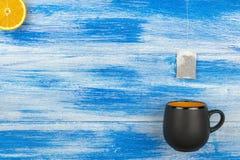 Filiżanka herbata na błękitnym tle Herbacianej torby i pomarańcze plasterki Lato Zdjęcia Royalty Free