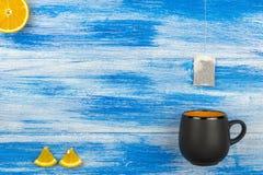 Filiżanka herbata na błękitnym tle Herbacianej torby i pomarańcze plasterki Lato Obrazy Royalty Free