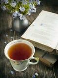 Filiżanka herbata, rocznik książki i błękit, kwitnie na stole Fotografia Stock