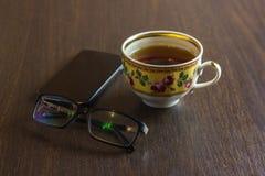 Filiżanka herbata, telefon komórkowy, ołówek, szkła na drewnianym biurowym desktop Zdjęcie Royalty Free