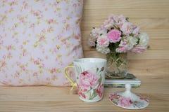 Filiżanka herbata, waza różowe róże i poduszki, Zdjęcia Stock