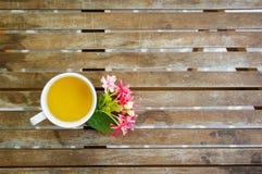 Filiżanka herbata z ładnymi kwiatami na drewnianym stole w ogródzie Obraz Royalty Free