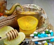 Filiżanka herbata z cytryną, pigułkami, termometrem i ciepłym szalikiem, Witaminy herbata zimno grypa lekarstwo zdjęcia royalty free
