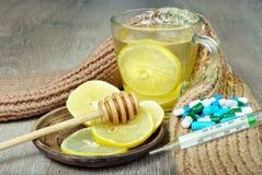 Filiżanka herbata z cytryną, pigułkami, termometrem i ciepłym szalikiem, Witaminy herbata zimno grypa lekarstwo zdjęcie stock