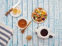 Filiżanka herbata z cytryną, teapot i wysuszonymi owoc na drewnianym stole, Obraz Royalty Free