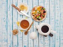 Filiżanka herbata z cytryną, teapot i wysuszonymi owoc na drewnianym stole, Zdjęcie Stock
