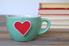 Filiżanka herbata z kierową kształtną herbacianej torby etykietką Zdjęcie Stock