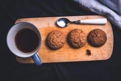 Filiżanka herbata z oatmeal łyżką na drewnianej desce i ciastkami zdjęcia royalty free