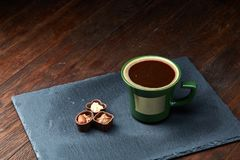 Filiżanka i czekoladowi cukierki na kamieniu wsiadamy nad drewnianym tłem, selekcyjna ostrość, zakończenie Obrazy Royalty Free